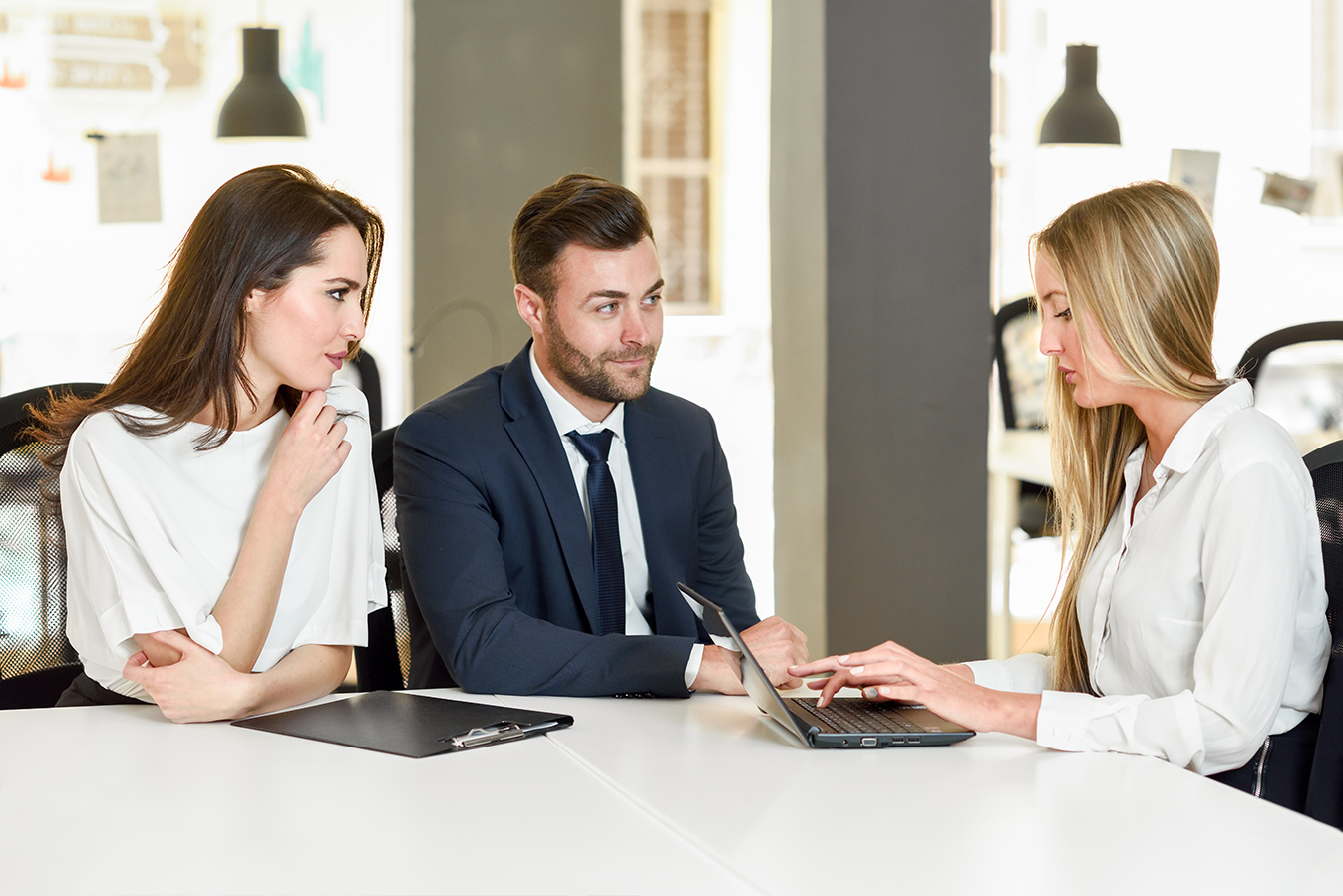 Blonde woman insurance agent or investment adviser explaining with laptop computer to a smiling young couple.