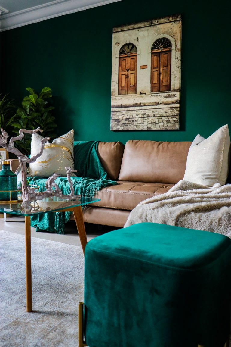 Forest green walls, brown leather sofa, plus decor in gold, cream, green and greys.