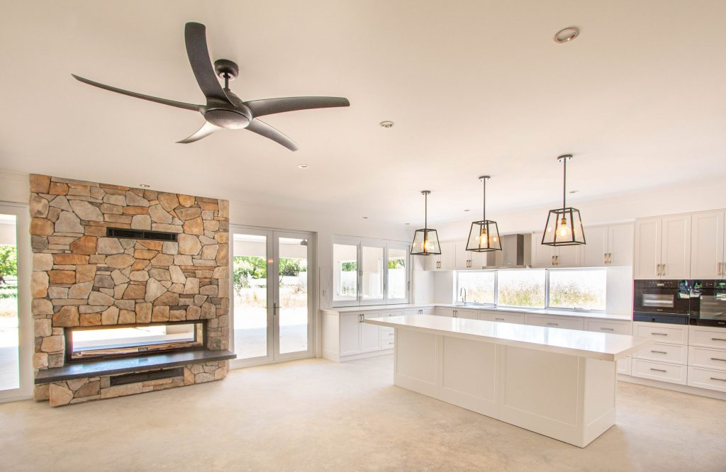 Rural Kitchen with stone fireplace and pendant lighting
