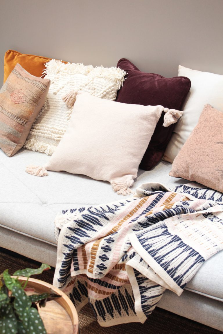 Cushions in pale pastel tones and a patterned throw rug on a grey sofa.