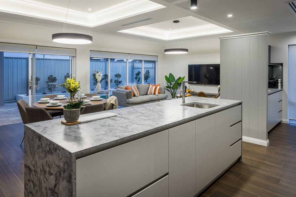 Kitchen with large marbled stone benchtop, looking towards an open plan living area and alfresco outside.