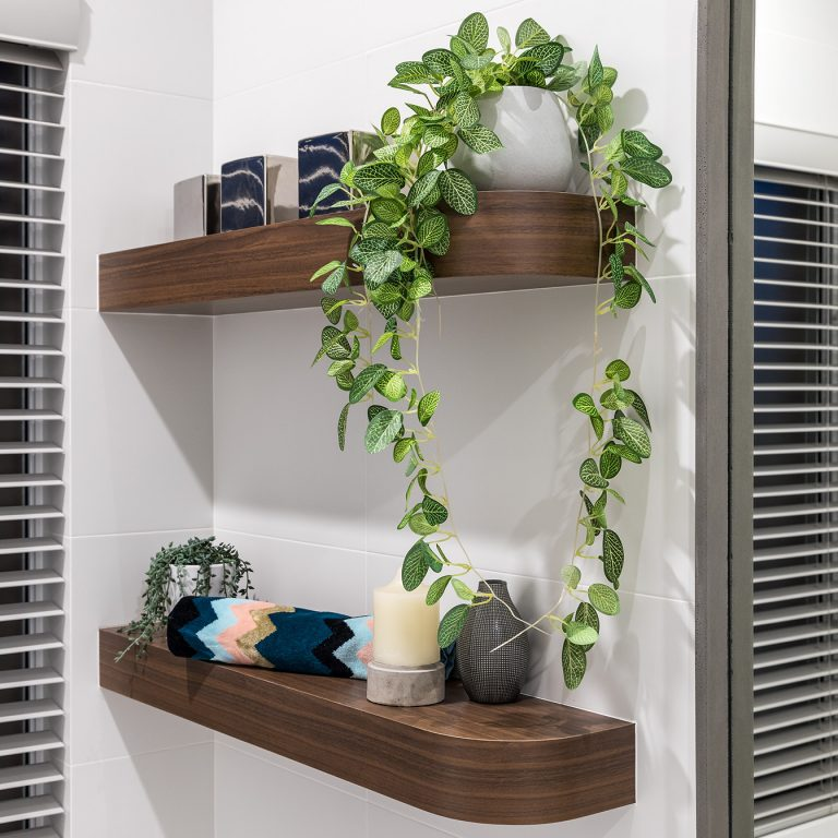 Two wooden bathroom shelves, complete with candles and draping leafy plants.