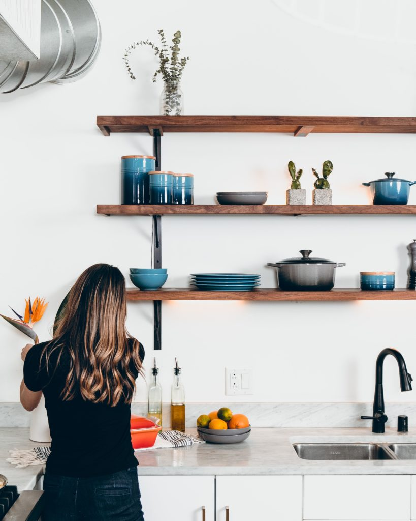 Woman in white kitchen with wooden shelves and blue crockery, arranging flowers